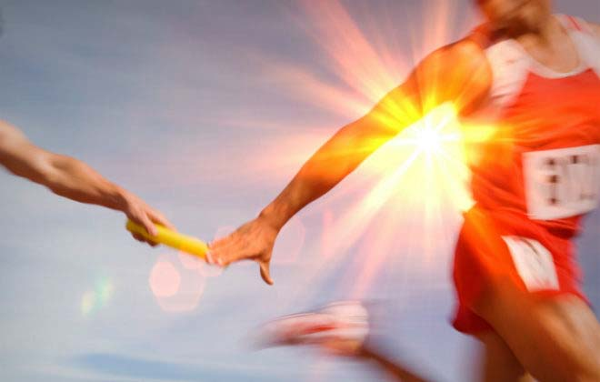 A runner hands off a baton to another runner to symbolize preparing for businesses succession runners